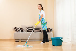 young woman cleaning her hardwood floor